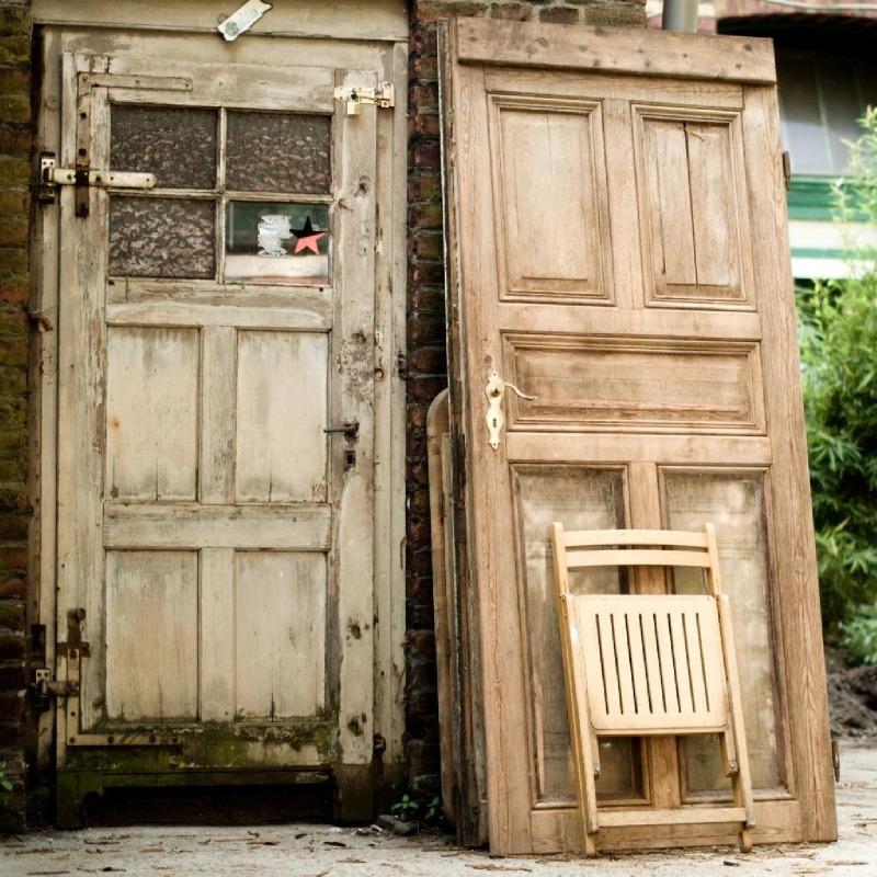 Eine alte Tür mit einem kleinen schwarz/roten Strern und noch eine Tür, die daneben an der Wand lehnt